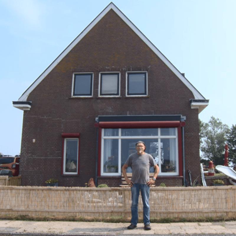 Wij zien een foto van een man, Frans Houtman. Hij staat voor zijn huis, op Kornwerderzand. Linksboven is het hartjes-logo van Omrop Fryslân.