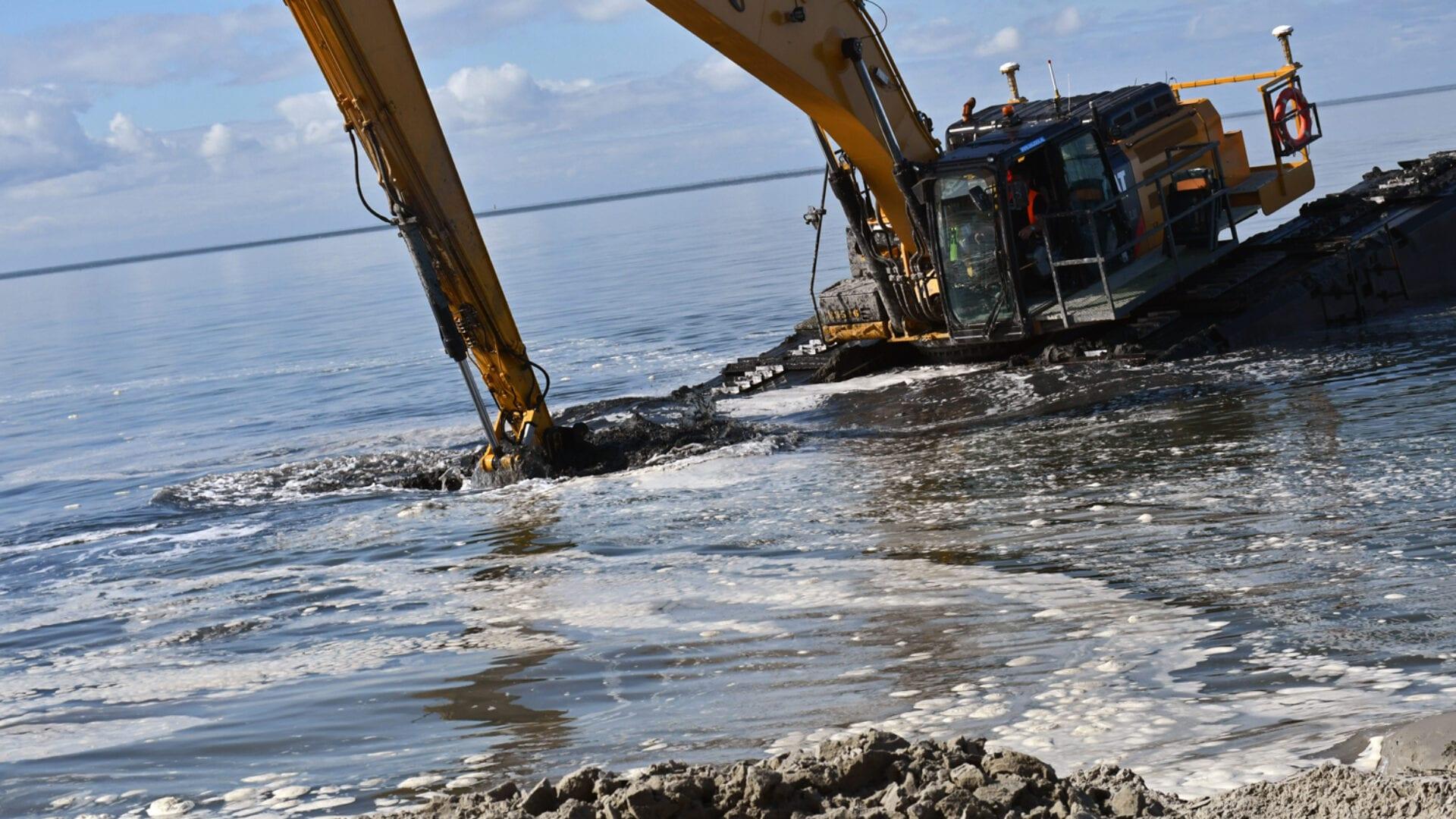 Wij zien het water bij Kornwerderzand. Aan de voorkant liggen zand en stenen. Daarachter water en er drijft een amfibiekraan in. Deze is bezig om grond te verschepen.