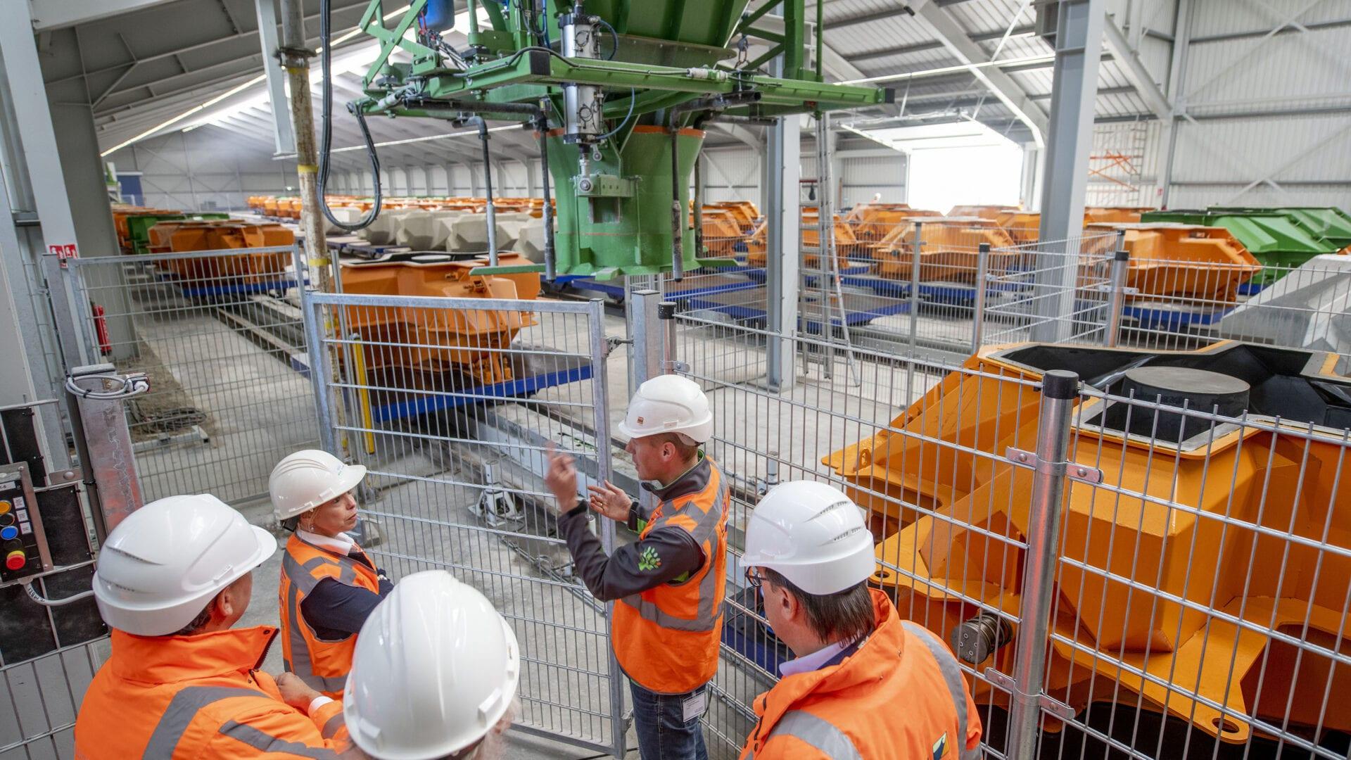 Wij staan binnen in een loods. Daar zien wij de openingshandeling door Avine Fokkens. Zij staat voor een hek met een aantal werkmannen. Op de achtergrond staan veel gele blokken.
