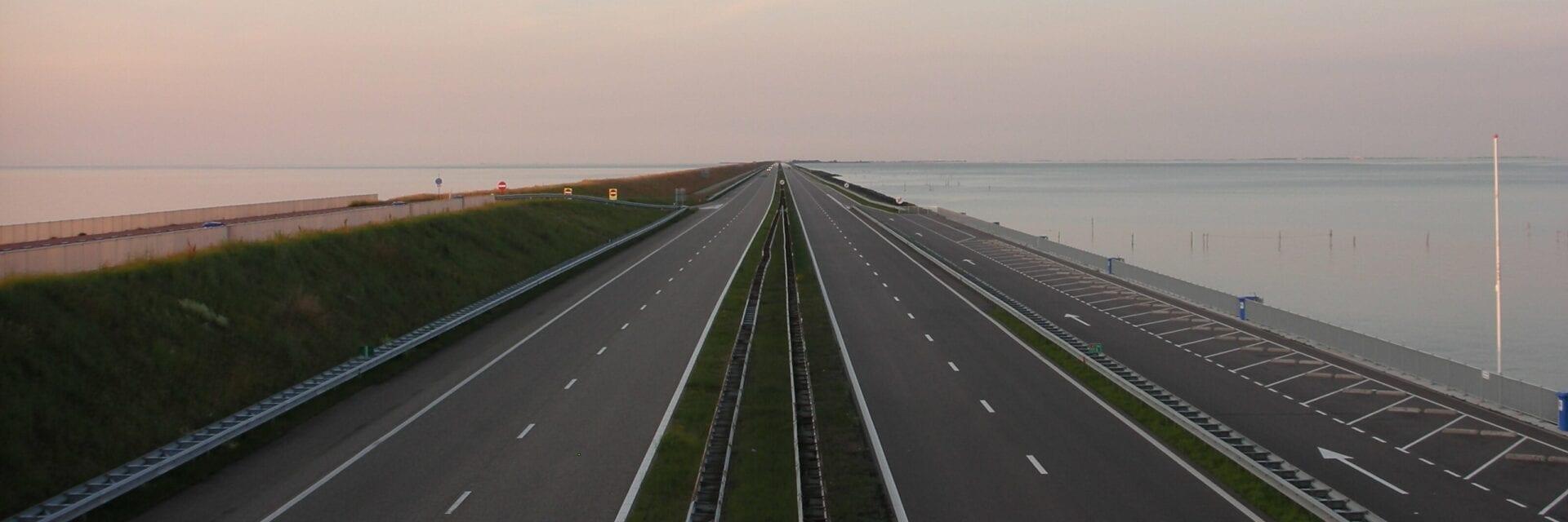 Wij zien een foto van de wegdelen bij de Afsluitdijk. Er zijn vijf stroken. Op de achtergrond zien we de gekleurde lucht van een zonsondergang. Aan de zijkant zien wij het IJsselmeer.