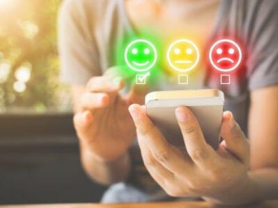 Graphic met smileys voor de tevredenheidsmetingen. Er zijn drie smileys, groen en geel en rood. Op de achtergrond zit een persoon met een witte telefoon.