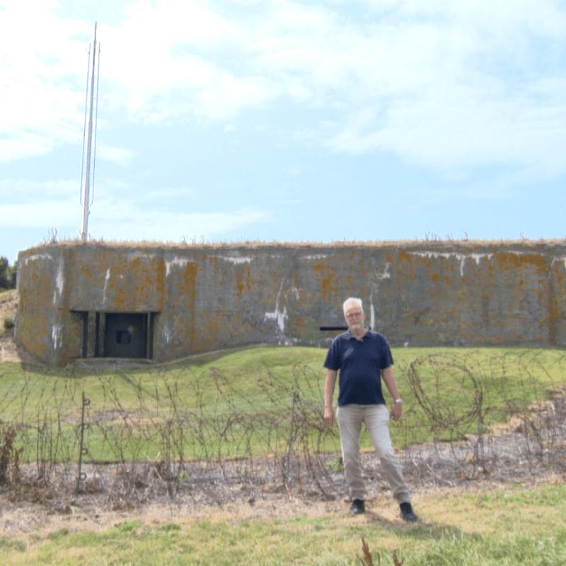 Op de afbeelding staat een man. Hij staat voor de bunkers van de Kazematten. Aan de linkerkant staat ook een gestreept lokethuisje.