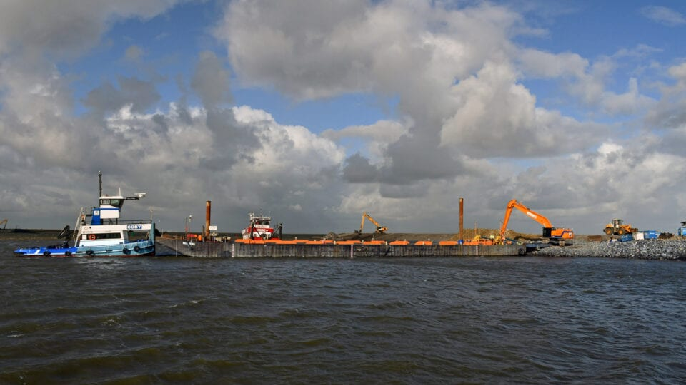 Wij kijken uit over het water. Er ligt een boot in het water en een oranje kraan. Deze voeren werkzaamheden uit aan de dam: De Banaan.