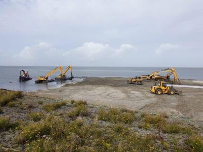 Wij zien op de voorgrond van de foto duinplanten. Daarachter ligt zand. Er zijn vier gele wagens bezig om het zand te scheppen.