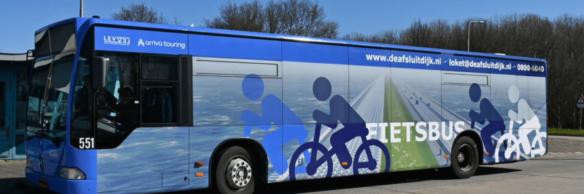 Op de foto staat een blauwe fietsbus. Op de bus staat een tekening van drie fietsers en een afbeelding van de Afsluitdijk.