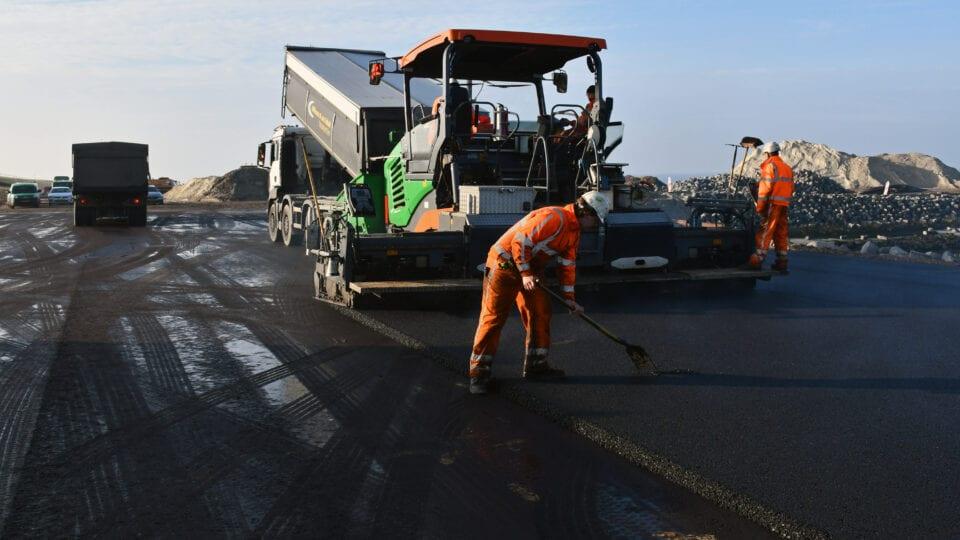 We zien twee mensen in oranje jassen bezig met asfalteringswerkzaamheden. Je ziet een stuk weg en een machine om de weg bij te werken.