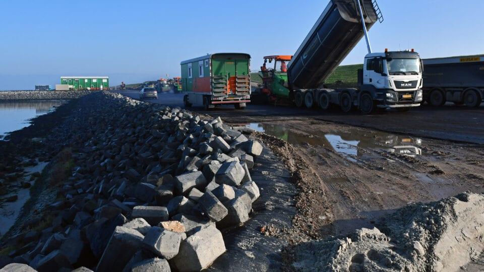 Wij zien een stukje van de dijk. Er staan meerdere vrachtwagens die bezig zijn met asfalteringswerkzaamheden. Aan de zijkant van de dijk liggen grote stenen.