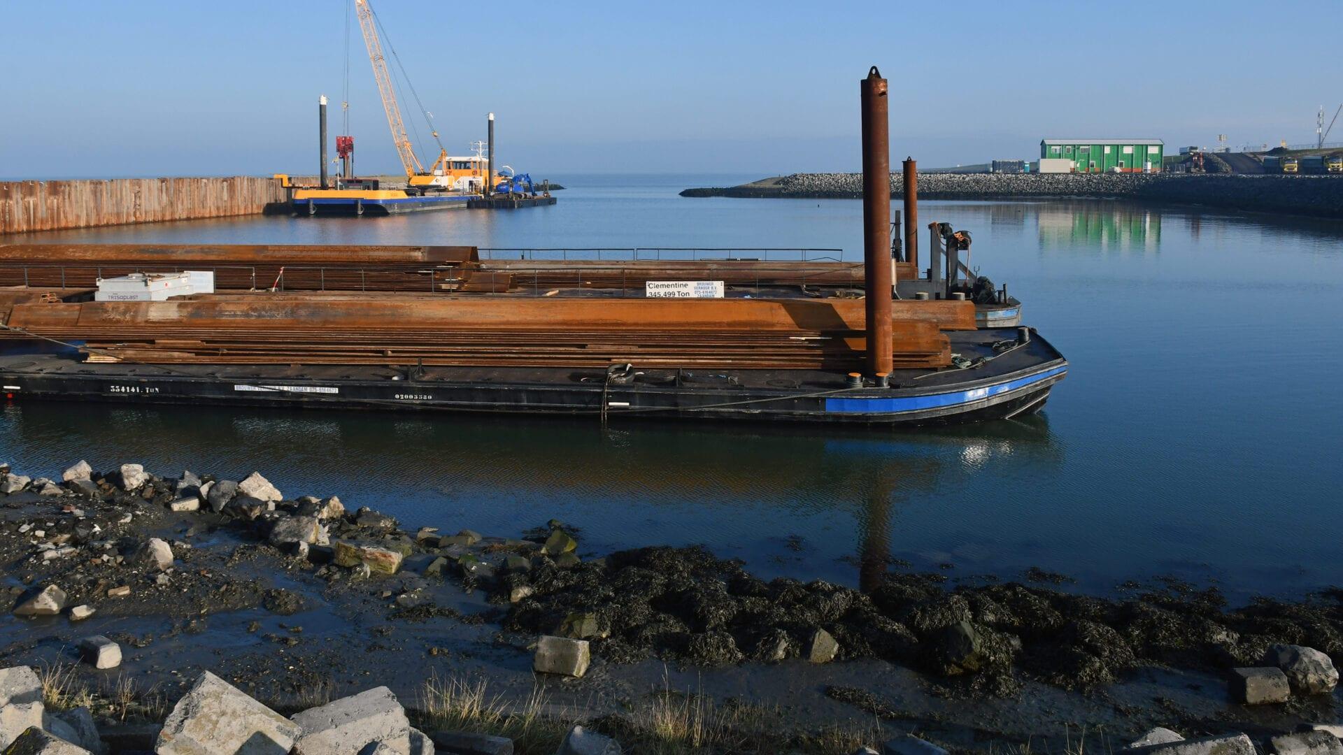 Wij zijn een stukje van grond en veel water op de achtergrond. Er ligt een boot in het water met roestkleurige pijpen en platen. Dit zijn damwanden die klaarliggen.