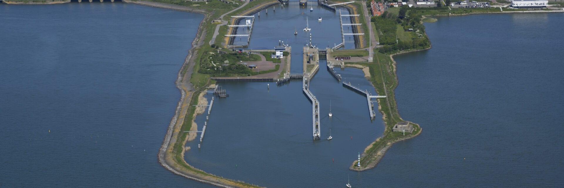 Wij zien een luchtfoto van de Schutsluizen bij Kornwerderzand. Van links naar rechts loopt een weg. Verticaal lopen vier landstroken met sluizen en boten. Aan beide kanten van de weg zie je water.