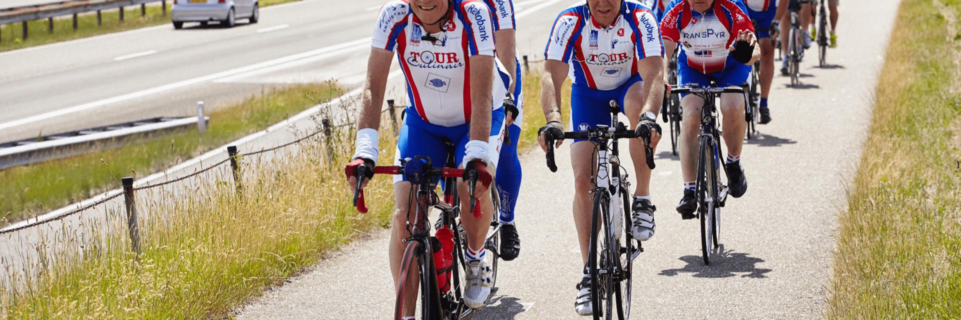 Wij zien een peloton aan fietsers die over het pad naast de weg op de Afsluitdijk rijden.