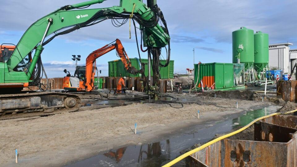 We zien een werkterrein met groenen kranen, loodsen en metalen silotanks. Er staat ook een oranje huiskraan. Ze brengen een bouwkuip aan.