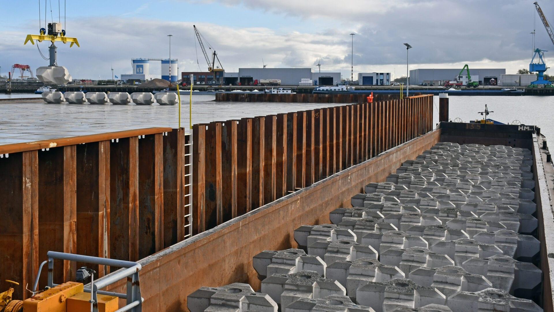 Wij zien een een industriegebied met blokken. De Levvel blocks liggen klaar voor transport naar de Afsluitdijk. Op de achtergrond zie je witte loodsen.