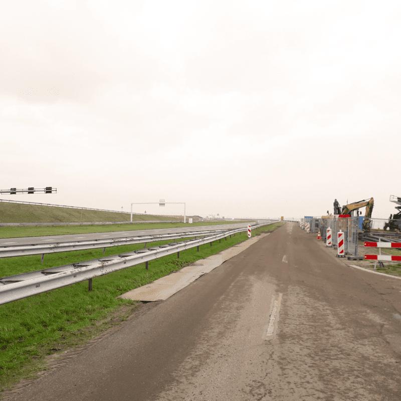 Wij zien een parallelweg die langs de weg bij Kornwerderzand loopt. De parallelweg is bruin en er staan rood-witte hekken naast.