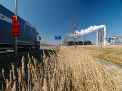 Wij zien een weg met vrachtverkeer dat eroverheen rijdt. Het havengebied Westpoort Amsterdam staat op de achtergrond met een grote pijp en rook.