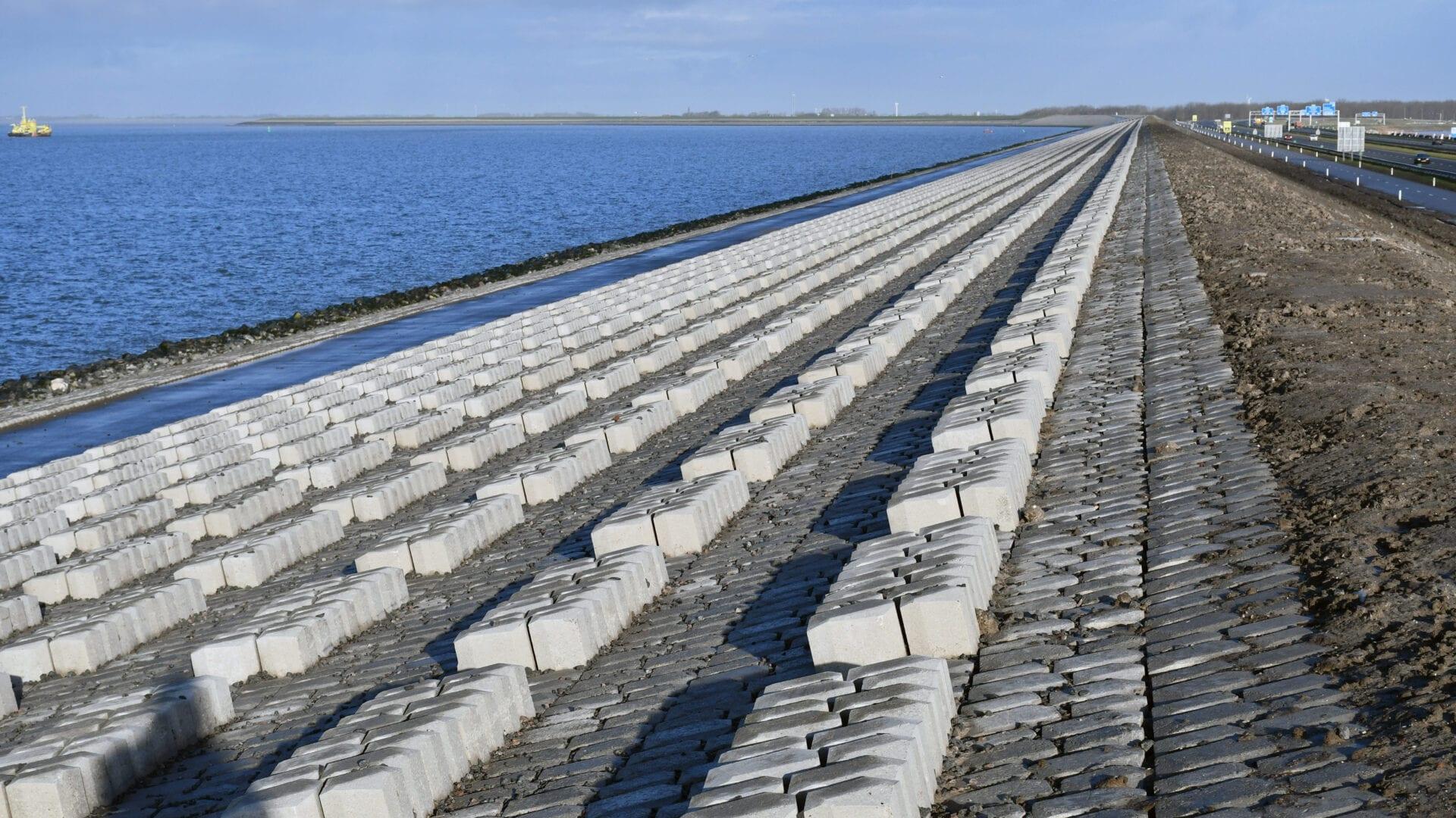 Je ziet een foto van de Quattroblocks bij de Afsluitdijk. Dit zijn blokken die aan de zijkant van de dijk liggen. Aan de linkerkant zie je het water van de Waddenzee.