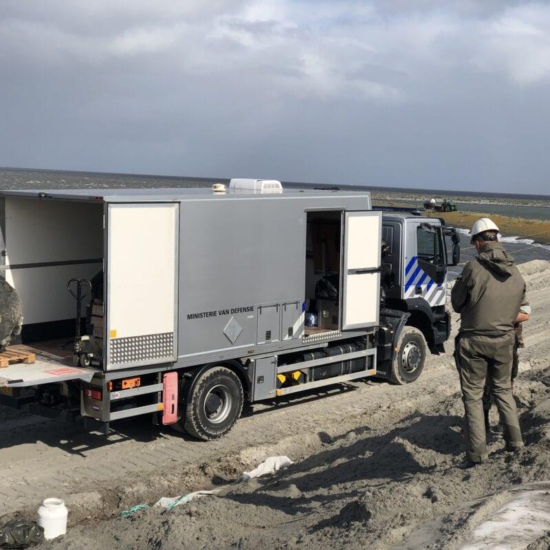 Je ziet een grijze bus bij de Afsluitdijk. Er is een explosief gevonden. Een grote bal wordt door een graafmachine in de bus getild. Aan de zijkant staan drie mannen te kijken.