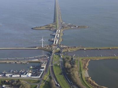 Luchtfoto. Voor zie je de haven en sluizen van Den Oever. Je ziet de weg van de Afsluitdijk recht naar boven lopen. In het midden van de weg ligt een bredere landstrook.