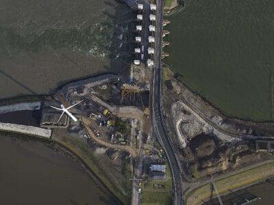 Luchtfoto van het werk op de Afsluitdijk. De foto is gemaakt bij de witte sluisgebouwen, die zie je boven aan de foto. Onder de sluisgebouwen zie je een werkterrein. Deze is grijs met een paar bruine wegen. Van boven kijk je op de windmolen.