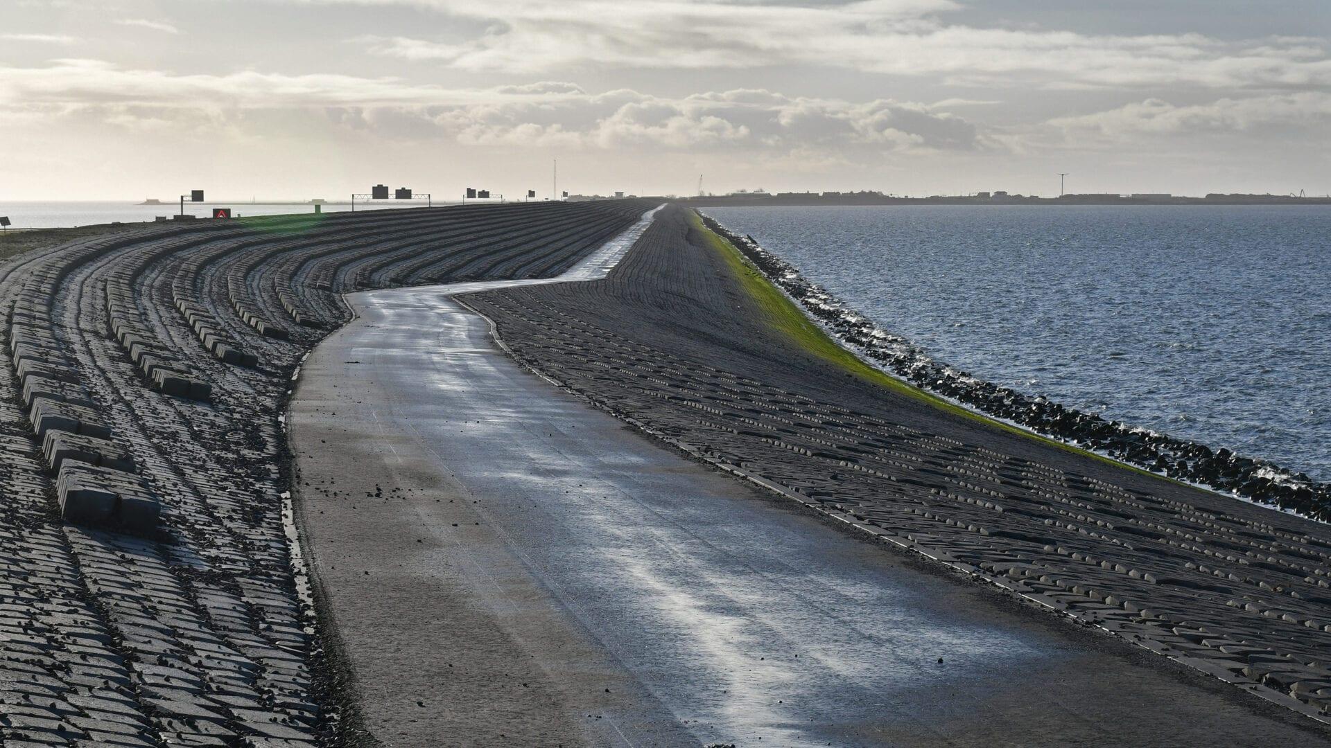 Je ziet een foto van de Quattroblocks bij de Afsluitdijk. Dit zijn blokken die aan de zijkant van de dijk liggen. Aan de rechterkant zie je het water van de Waddenzee. Links loopt de autoweg.