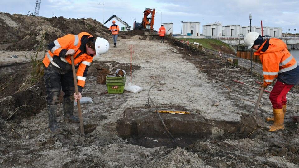 Je ziet twee mensen in oranje jassen archeologisch veldonderzoek uitvoeren. Zij zijn bezig met graven in het zand bij de Afsluitdijk. Op de achtergrond zie je witte sluisgebouwen.
