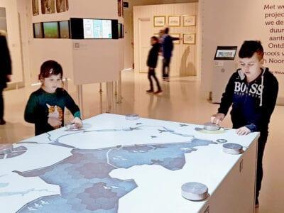 We zien een tafel in het Afsluitdijk Wadden Center. Op de tafel zie je een blauwe weergave van een stuk land. Op de tafel staan ook een paar knoppen en twee kindjes spelen er mee. Op de achtergrond zie je witte wanden met teksten.