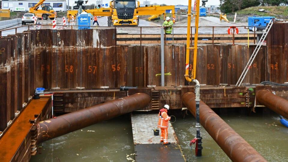 Wij kijken in de bouwkuip bij het gemaal. Deze is omringt door metalen muren. Aan de onderkant van de kuip staat water. In het water ligt een ponton en er staat een man op. Aan de bovenkant zie je werklui en een gele vrachtwagen.