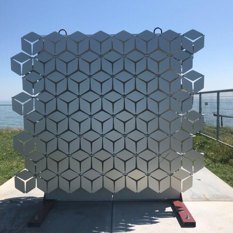 Wij zien een beeld dan uit verschillende zilvere, plate, blokjes bestaat. Dit is de proefopstelling van Gerben Vos. Op de achtergrond zie je een hek en daarachter de zee.