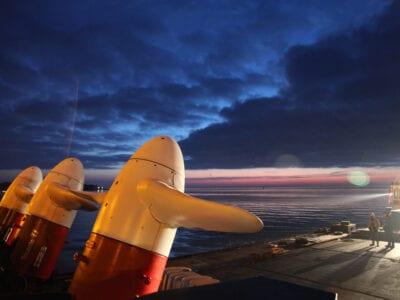 We zien een donkere hemel met een zonsondergang. Voorin zie je drie, wit en rode turbines. Daarachter drijft een ponton in het water. Er staan twee mensen op.