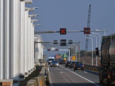 Wij kijken op de weg van de Afsluitdijk. Aan de linkerkant zie je de gebouwen van de Stevin Sluizen. Op weg rijdt veel verkeer. Boven de weg hangen borden. 1 met een kruis en 1 met 50km.