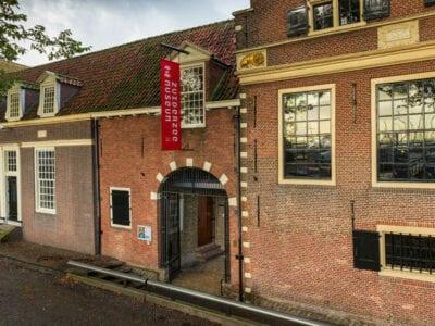 We zien het gebouw van het Zuiderzee-museum. Het is een oud bruin gebouw met wittige ramen. Aan de geval hangt een rode vlag met het logo. De poort daaronder is open.
