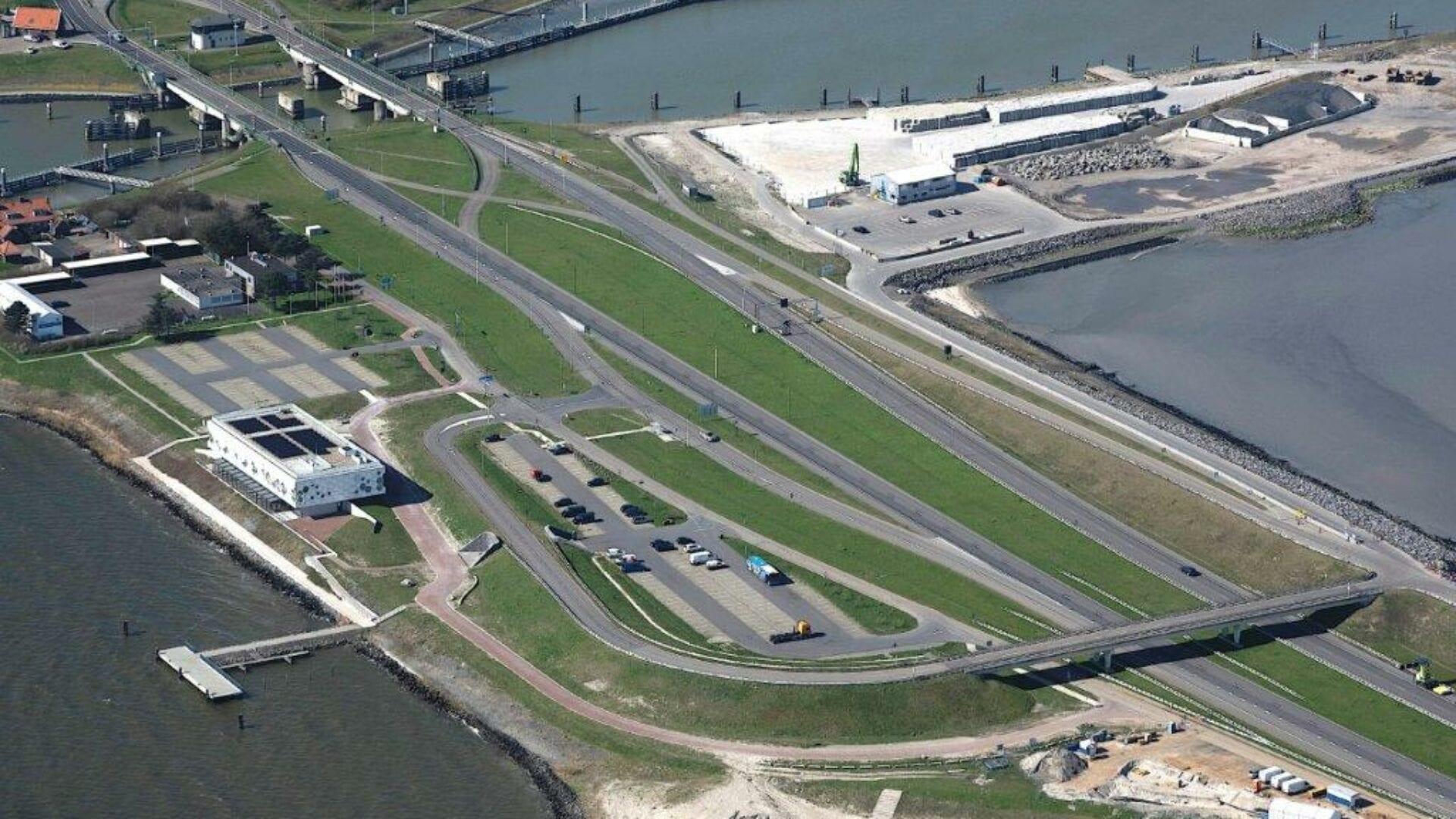 Luchtfoto van het Afsluitdijk Wadden Center. Wij kijken van boven op het museum. Daarnaast zie je de wegen die op de Afsluitdijk zijn. Er loopt ook nog een horizontale weg over de weg. Rechtsboven zie je een werkterrein met zand en stenen.