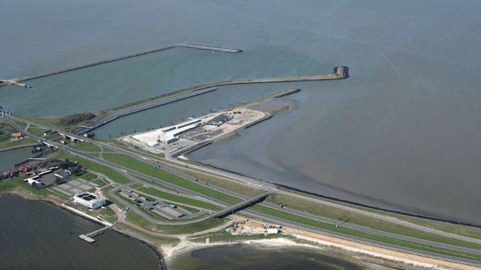 Luchtfoto van het werkeiland bij Kornwerderzand. Van links loopt de weg naar rechtsonder. Je ziet een stukje van het surfstrand en aan de linkerkant het witte gebouw van het Afsluitdijk Wadden Center.