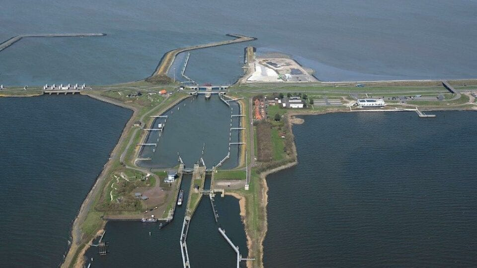 Luchtfoto van de sluizen bij Kornwerderzand. Van links naar rechts loopt de weg van de Afsluitdijk. In het midden zie je twee landstroken van boven naar onder lopen. Dit is de sluis bij Kornwerderzand. Je ziet in de verte een paar rode daken van Kornwerderzand en het kantoor van DNA en het witte gebouw van het Afsluitdijk Wadden Center.