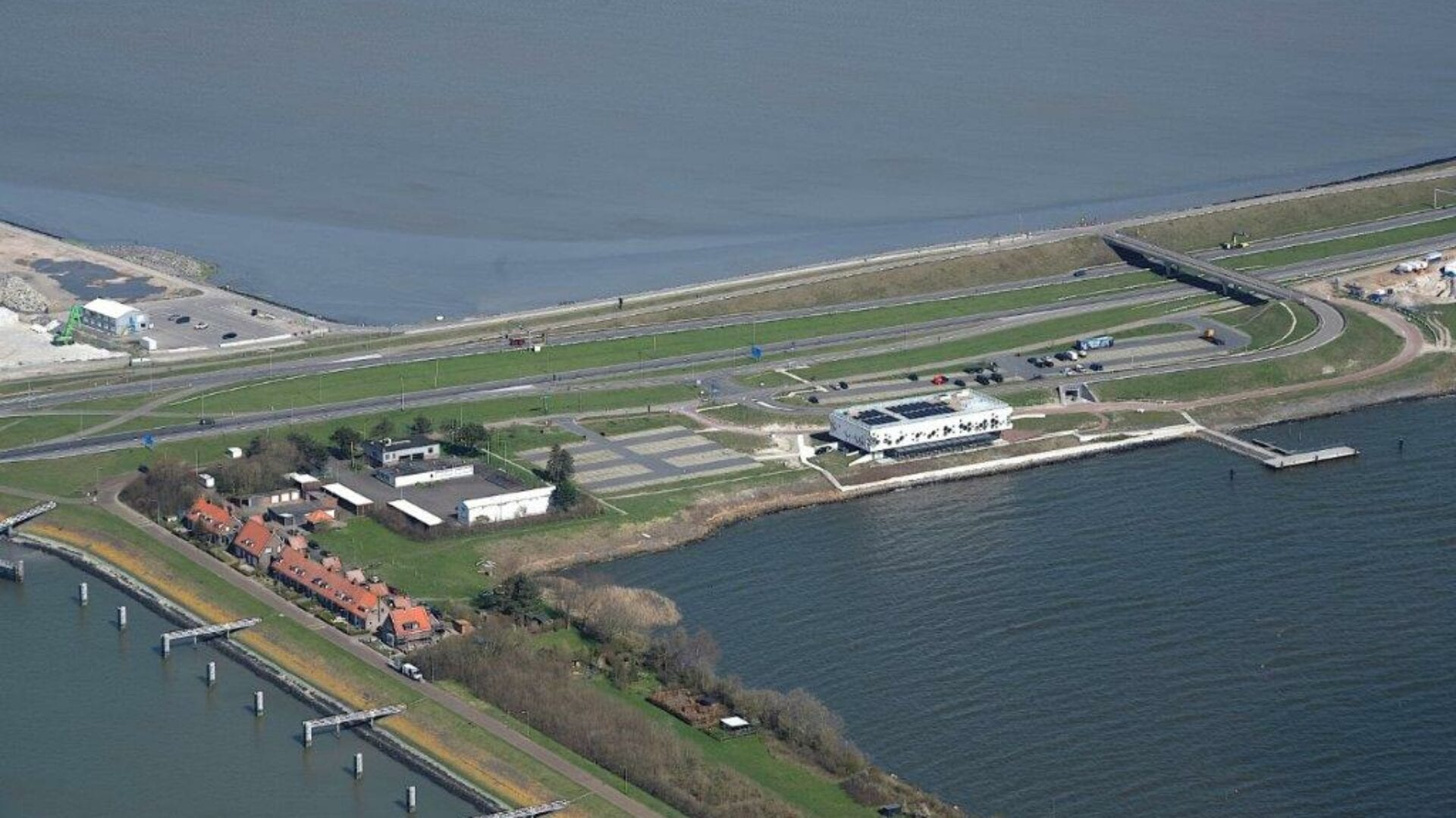 Luchtfoto van het Afsluitdijk Wadden Center. Horizontaal zie je de weg van de Afsluitdijk lopen. In het midden zien we de huizen van Kornwerderzand. Daarnaast het kantoor van DNA. Volgen wij de weg naar rechts dan zien we het witte gebouw van het Afsluitdijk Wadden Center. Je ziet de weg die over de Afsluitdijk loopt. Aan de beide kanten van de weg zie je water.