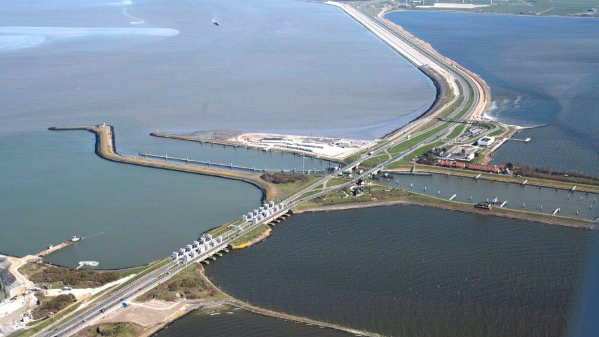 Luchtfoto van de sluizen bij Kornwerderzand. Je ziet van linksonder naar rechtsboven de weg en Afsluitdijk lopen. In de linkerhoek zie je een werkgebied. Daarna volgen we de weg en zien we de witte sluisgebouwen. Daarna zie je vier horizontale landstroken en rechts een beetje van Kornwerderzand. Aan het einde van de weg zie je een stukje van Fryslân.