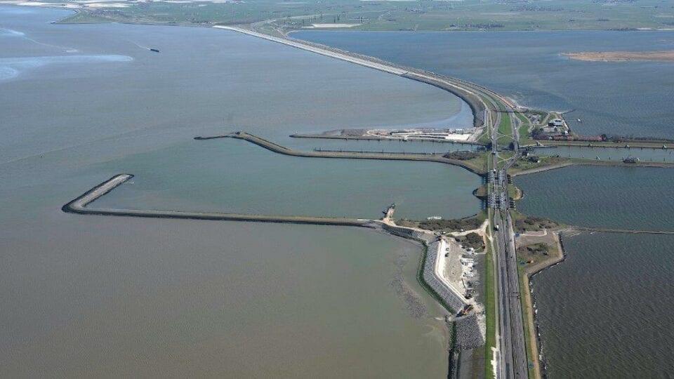 Luchtfoto van de Afsluitdijk en Waddenzee. Aan de rechterkant van de foto zien we de Afsluitdijk lopen. We zien aan de linkerkant een groot gedeelte van de Waddenzee. In het water liggen twee horizontale landstroken. Achter de laatste landstrook zie je ook een werkterrein met zand.
