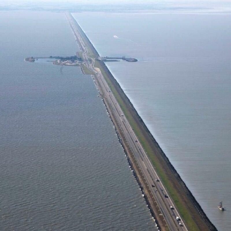 Luchtfoto van de weg op de Afsluitdijk. De weg loopt van beneden naar boven. In de verte zie je een stukje van Breezanddijk. Dit is een stukje land aan de weg.