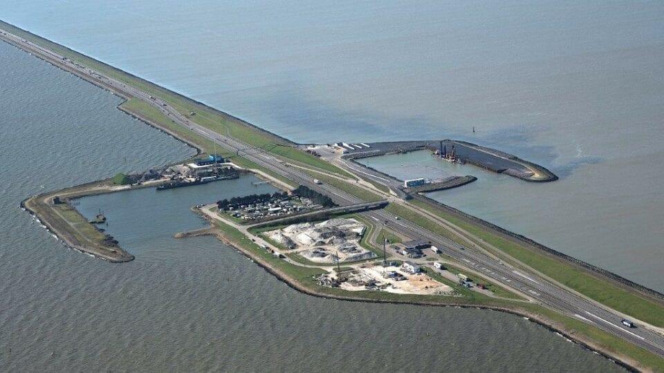 Luchtfoto van de Afsluitdijk. Wij kijken van boven op de haven en camping bij Breezanddijk. Je ziet de weg van linksboven naar rechtsonder lopen. Aan de zijkanten zie je water. De haven lijkt op een u, dit zijn landstroken waar boten kunnen aanmeren. Verder zie je een kleine camping en bouwterrein.