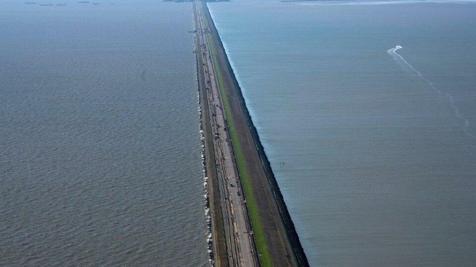 Luchtfoto van de Afsluitdijk. Wij kijken van boven op de weg, vanaf Den Oever. Je ziet de weg met aan beide kanten water. In de verte zie je een stukje van Fryslân.