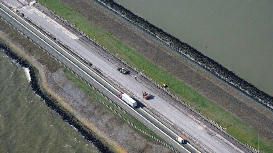 Luchtfoto van de weg bij de Afsluitdijk. Wij kijken van boven op de weg. Die loopt van linksboven naar rechtsonder. Deze wordt omringt door water. In het midden van de weg zie je een snelweg met auto's. In het midden zie je een witte vrachtwagen.