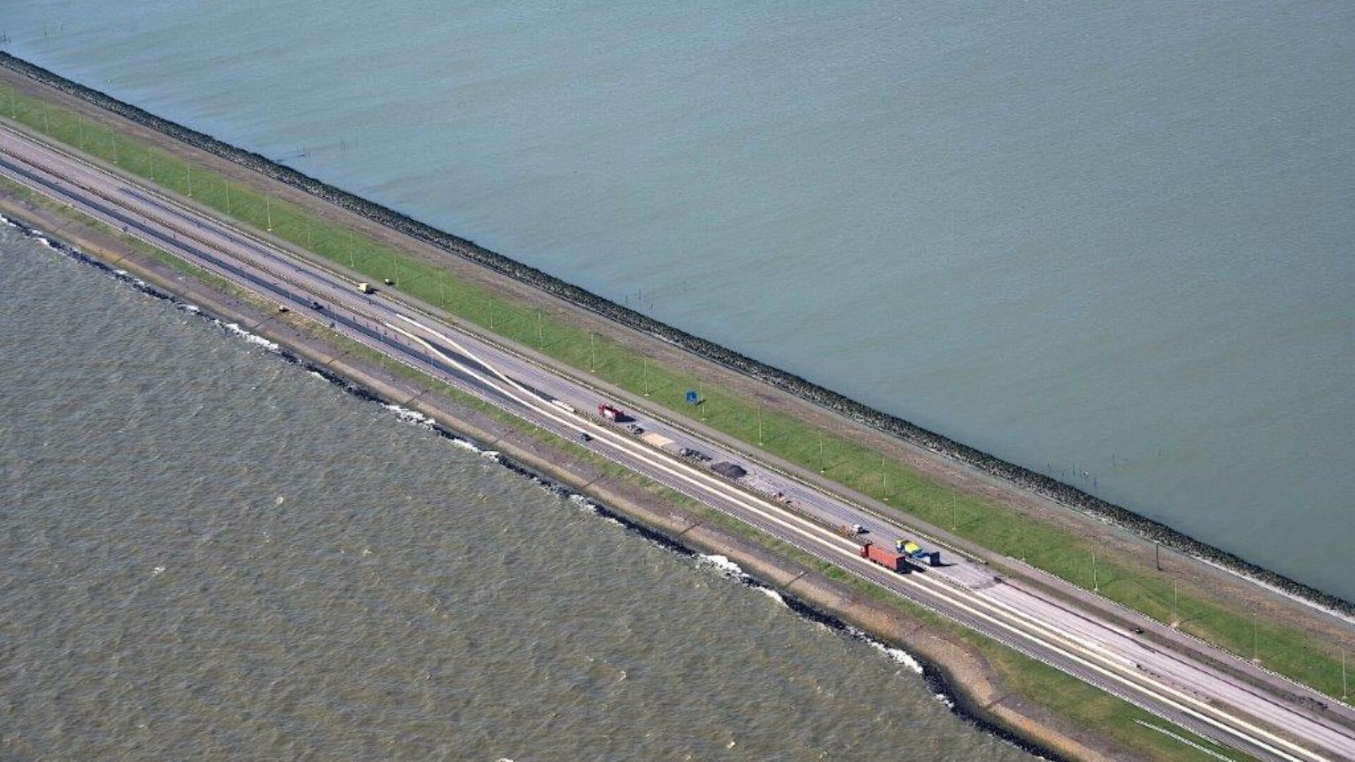 Luchtfoto van de weg bij de Afsluitdijk. Wij kijken van boven op de weg. Die loopt van linksboven naar rechtsonder. Deze wordt omringt door water. In het midden van de weg zie je een snelweg met auto's.