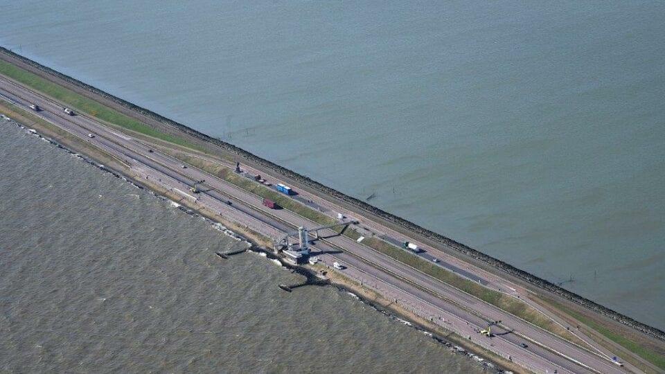 Luchtfoto van het monument bij de Afsluitdijk. Wij kijken van boven op de weg. Die loopt van linksboven naar rechtsonder. Deze wordt omringt door water. In het midden van de weg zie je een wit gebouw.