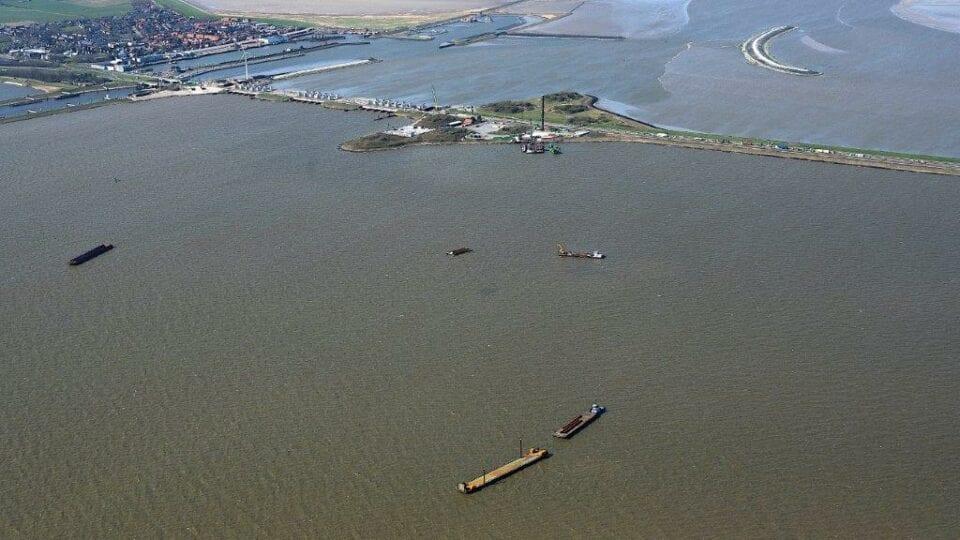 Luchtfoto van de Afsluitdijk. Dit is bijna bij Den Oever vanaf het IJsselmeer. Op grote hoogte kijken wij uit op het werkeiland bij Den Oever. Je ziet de Afsluitdijk van links naar rechts lopen. Je ziet sluizen, een banaanvormige landstrook in het water en een werkterrein.
