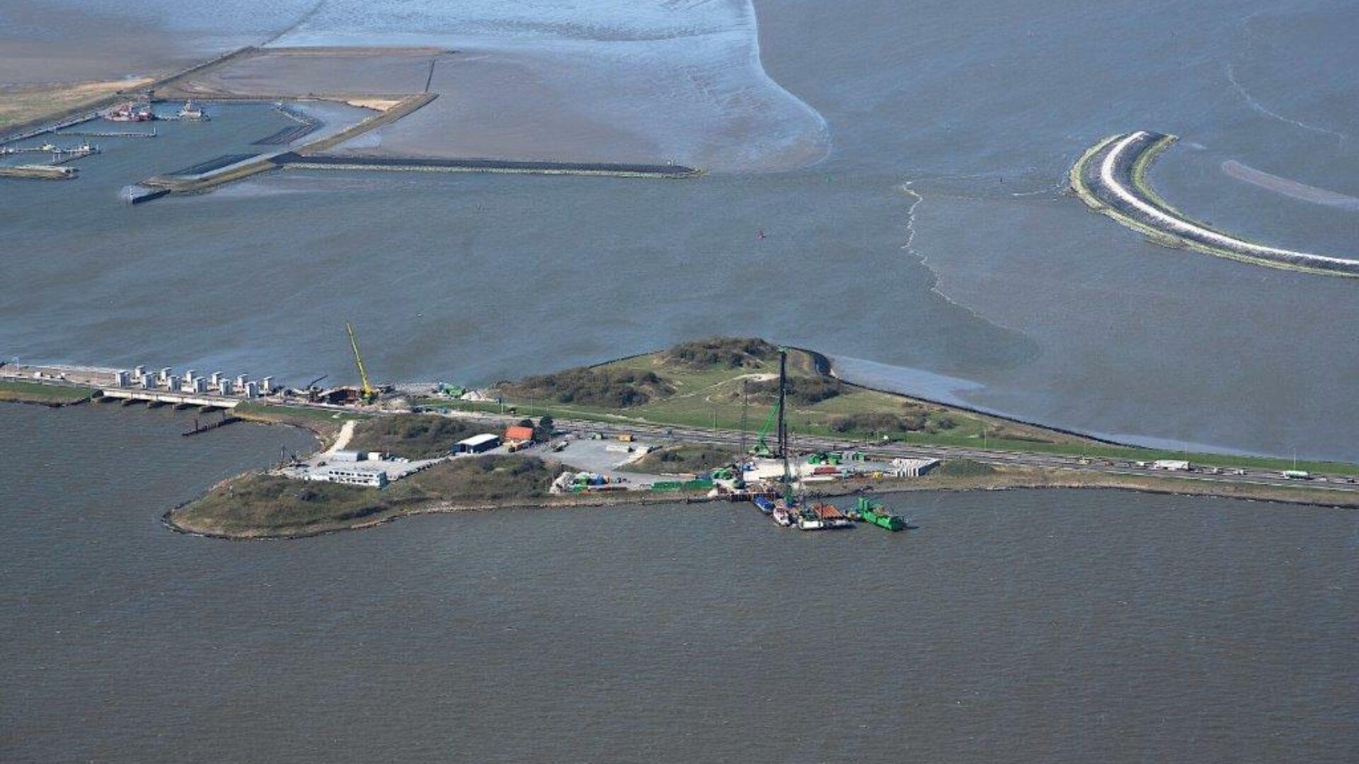 Luchtfoto van de Afsluitdijk. Dit is bijna bij Den Oever. Op grote hoogte kijken wij uit op het werkeiland bij Den Oever. Je ziet de Afsluitdijk van links naar rechts lopen. Je ziet sluizen, een banaanvormige landstrook in het water en een werkterrein.