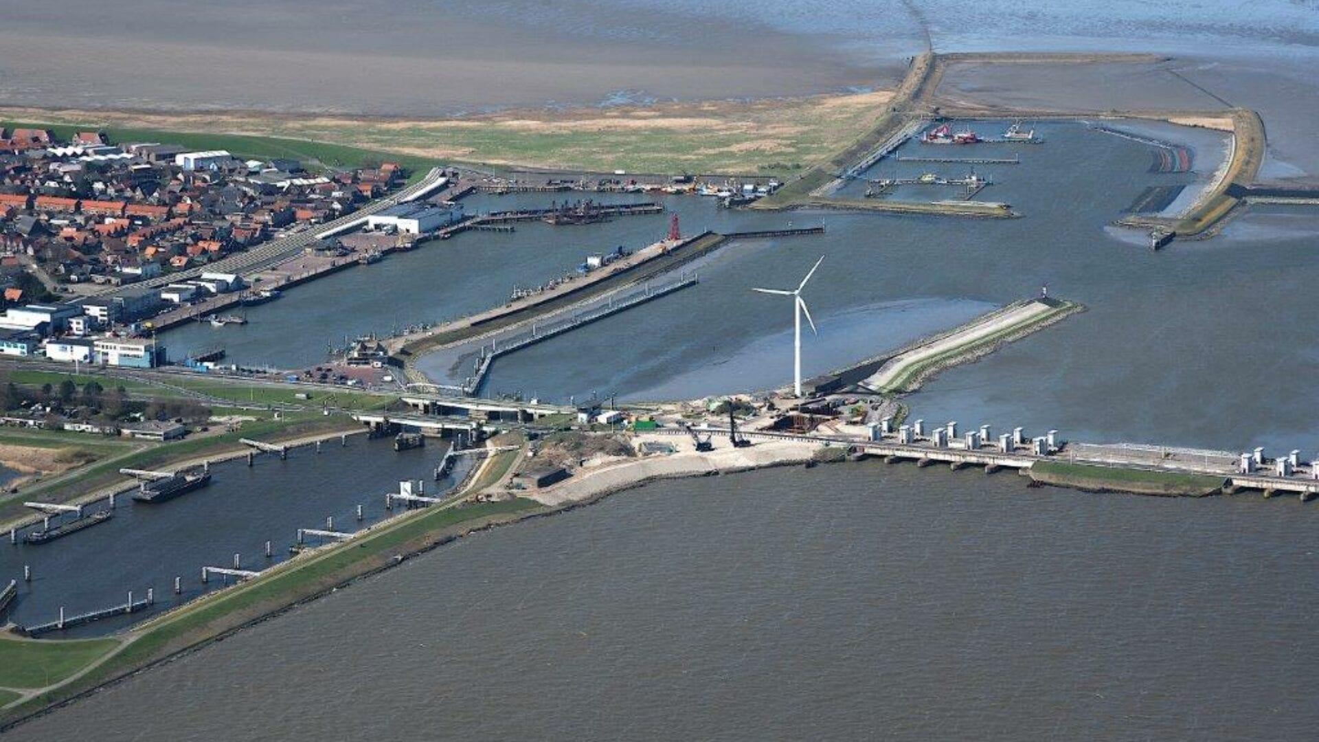 Luchtfoto van de Afsluitdijk en Den Oever. Wij zien aan de linkerkant een aantal huizen van boven. Vanaf die kant loopt de Afsluitdijk naar rechts. Je ziet een weg door het water lopen. Aan beide kanten zie je sluizen en landstroken in het water liggen.
