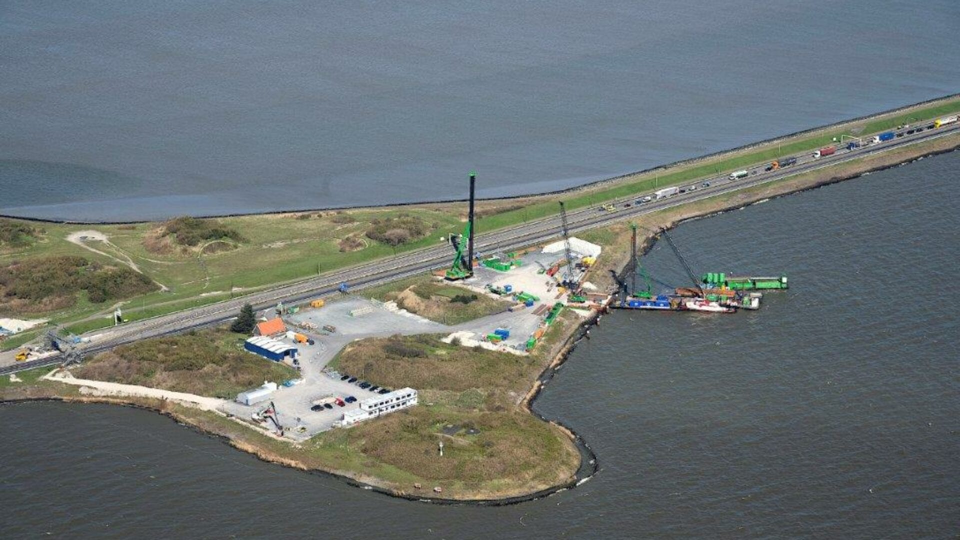 Luchtfoto van de Afsluitdijk. Wij kijken van boven op het graslandschap bij de Afsluitdijk. In het midden loopt de weg en daaromheen twee wateren van het IJsselmeer en de Waddenzee. In het graslandschap ligt een klein bouwterrein. Je ziet een blauw gebouw van Blue Energy en een groene heipaal met een aanliggende boot in het water.