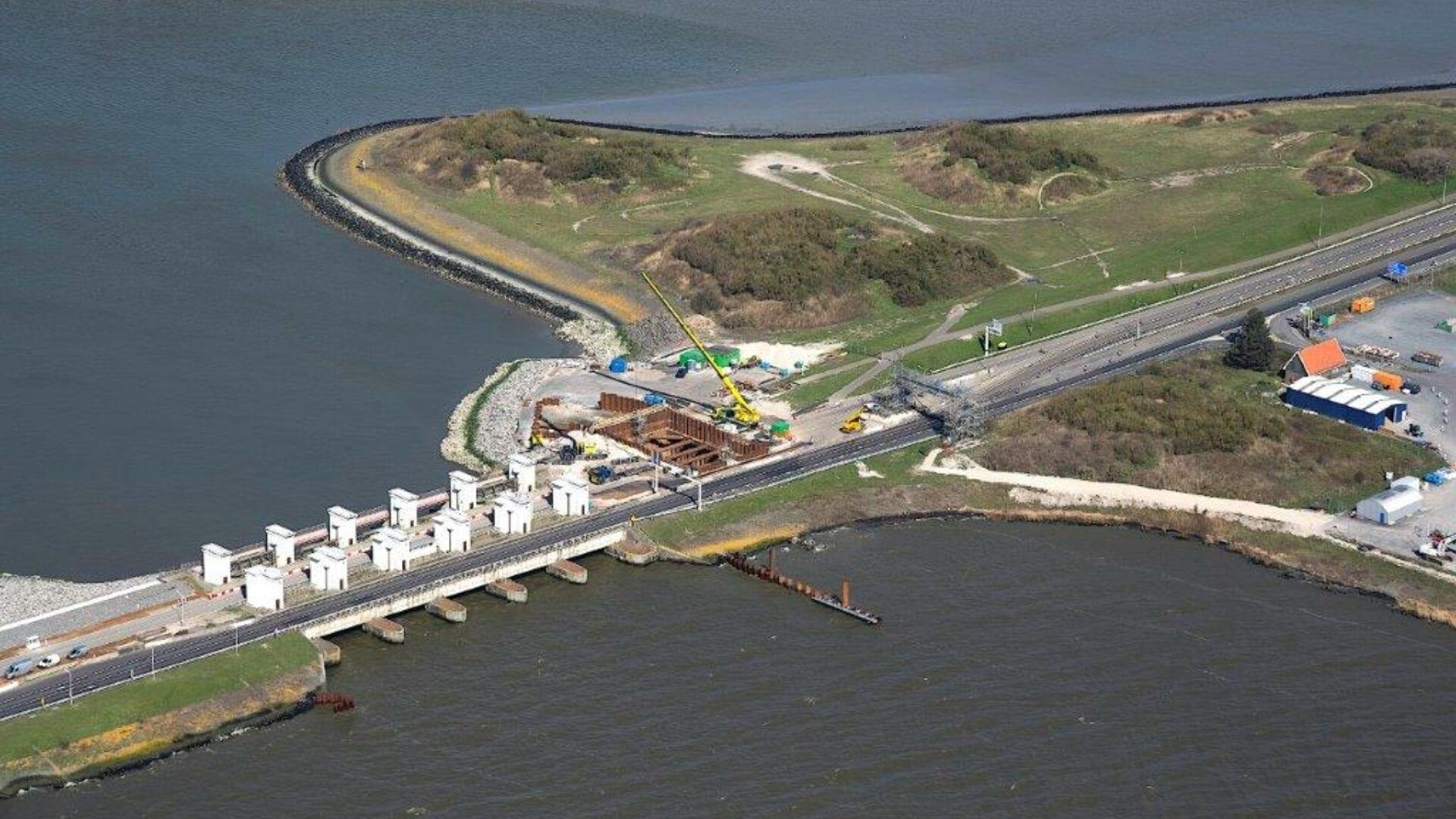 Luchtfoto van de Afsluitdijk. Wij kijken van boven op de Afsluitdijk bij de witte, voormalige sluisgebouwen, Gates Of Light. Je ziet boven en onder een klein stukje van de Waddenzee en het IJsselmeer. Links zie je de witte gebouwen van Gates of Lights. Rechts naast de witte gebouwen, zie je een graslandschap. Onder het landschap zie je een weg lopen. Daaronder zie je een blauw gebouw van Blue Energy.
