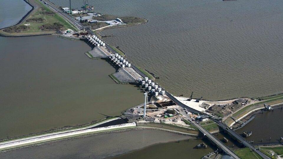 Luchtfoto van de Afsluitdijk. Van boven kijken wij op de Afsluitdijk ten hoogte van Den Oever. Wij zien de dijk schuin door beeld lopen. De Afsluitdijk ligt tussen twee wateren van het IJsselmeer en de Waddenzee. Voor in beeld ligt een bouwterrein met een windmolen. Daar achter zie je twee rijen van witte gebouwen, Gates of Lights. Daarachter zie je een groen gebied in het water, de weg en een klein bouwterrein. Links boven loopt de weg uit beeld.