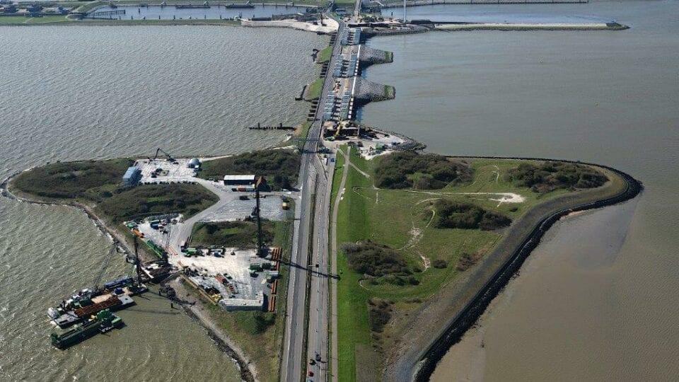 Luchtfoto van de Afsluitdijk. Van boven kijken wij op het bouwterrein bij de sluizen van Den Oever. Aan de rechterkant zie je een groen stuk landschap naast het water liggen. In het midden de weg van de Afsluitdijk en aan de linkerkant het bouwterrein. Verderop zie je kleine gebouwen op de weg, omringt door de twee wateren. Helemaal aan het einde is een begin van Den Oever.