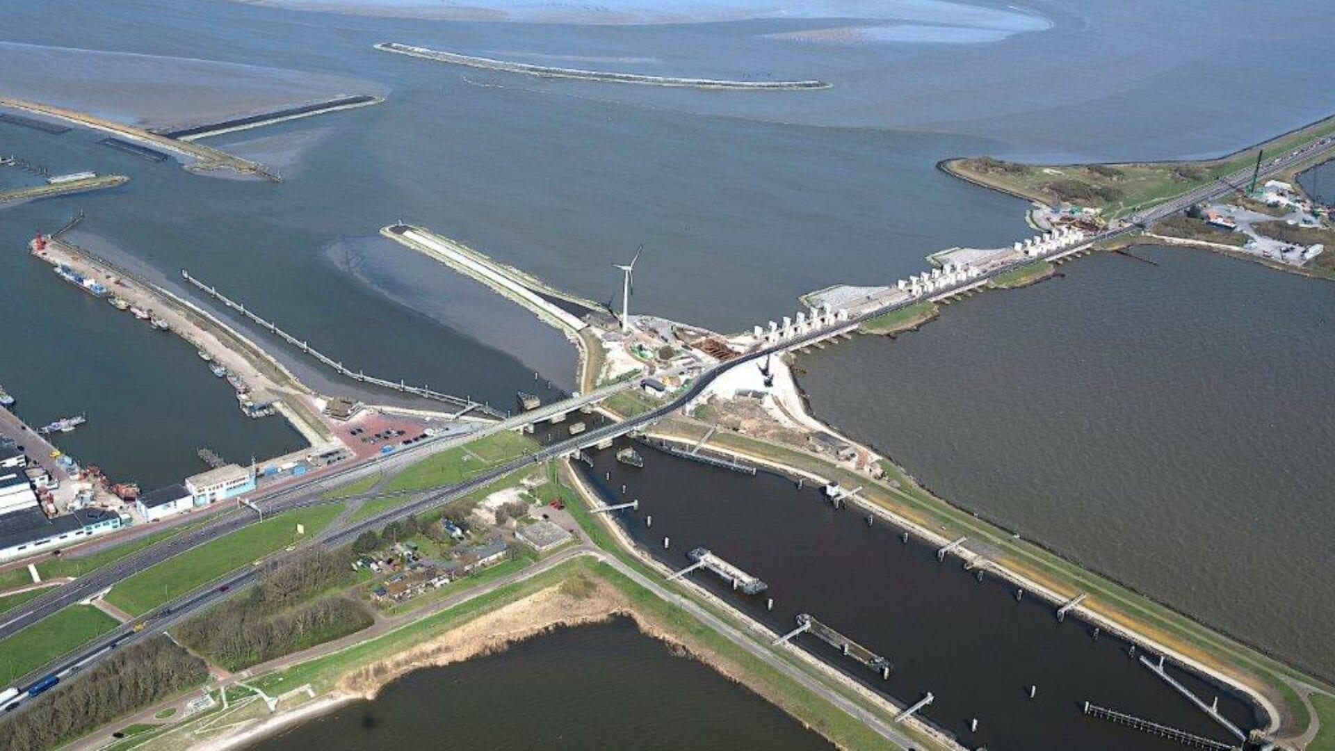 Luchtfoto van de Afsluitdijk. Je kijkt van boven, van de kant van het IJsselmeer, uit op de sluizen, witte gebouwen en een windmolen. Uit beeld loopt de lange Afsluitdijk naar achter. Aan weerskanten het water van het IJsselmeer en de Waddenzee. Bij de kant van het IJsselmeer zie je het water omringt met grond dat bij de sluis eindigt. Bij de kant van de Waddenzee zie je een uitstroom-haven.